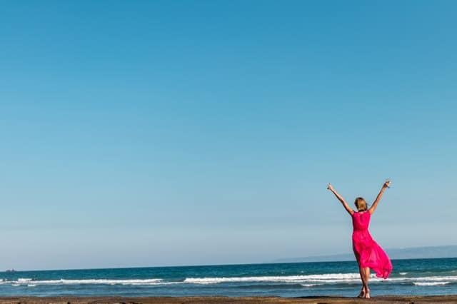 una mujer con un vestido rojo de pie en la costa