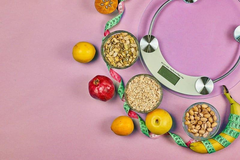 básculas de cocina y alimentos dietéticos saludables (granos, frutas)