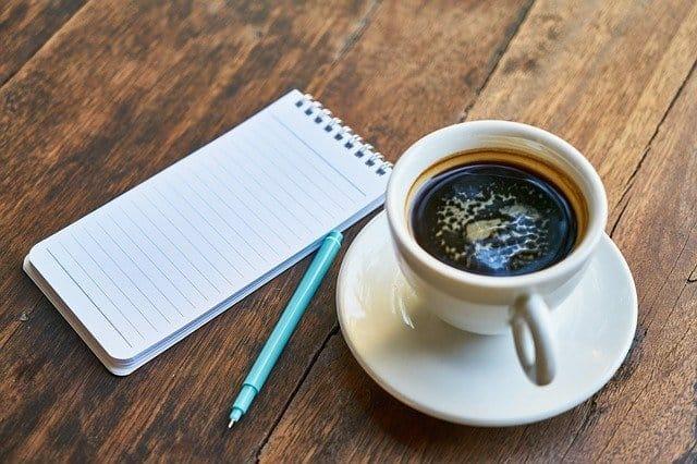 taza de café, bloc de notas, bolígrafo