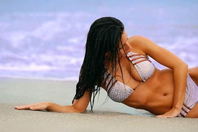 la mujer en traje de baño está tirada en la playa