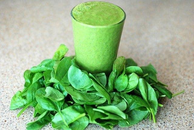 Un vaso con un batido verde, con hojas de espinacas alrededor