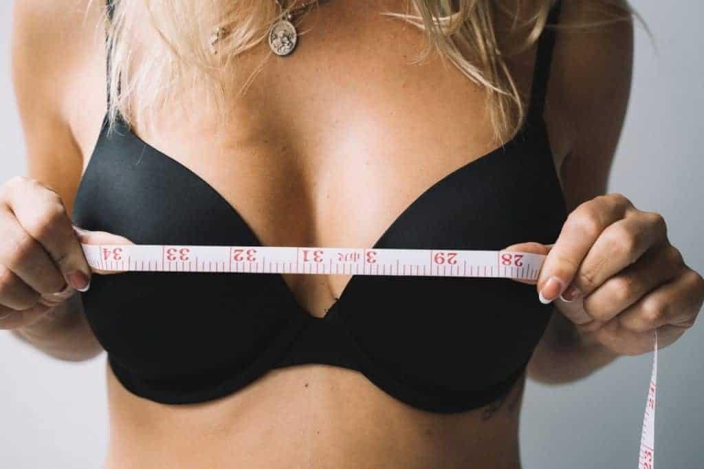 una mujer se mide los pechos con un centímetro