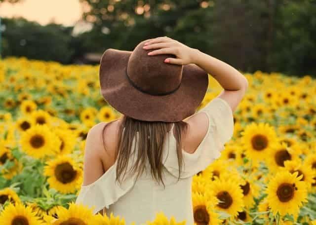 una mujer camina por un campo de girasoles