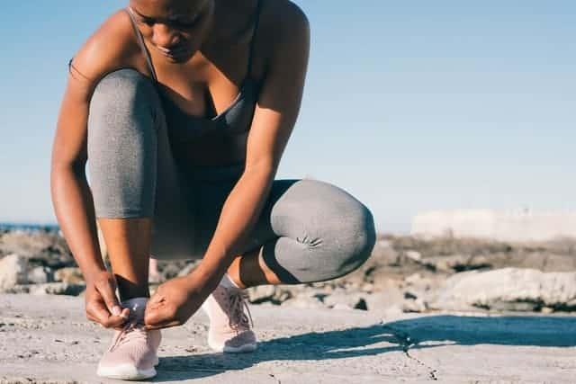 mujer en ropa deportiva se ata el zapato