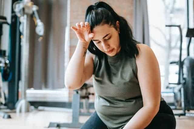 mujer con sobrepeso cansada después de un entrenamiento